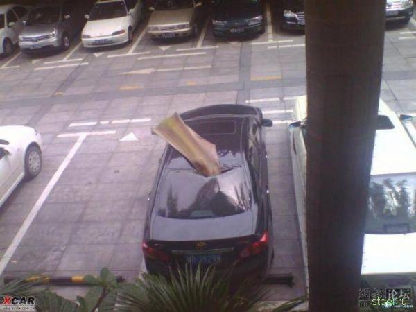 Инцидент на парковке: Куском кровли пробило крышу автомобиля (фото)